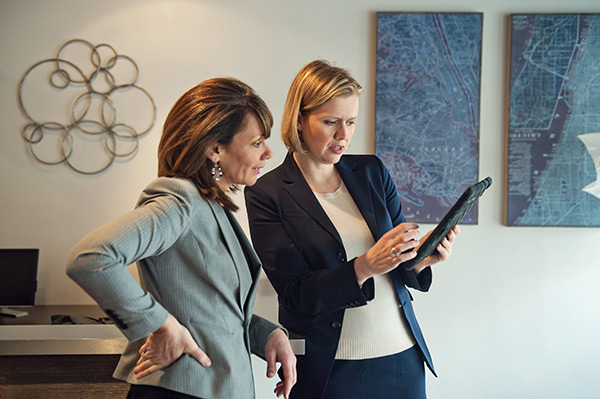 Jennifer Salvatore & Sarah Prescott looking at tablet.