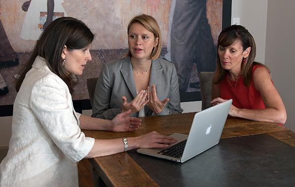 Julie Porter, Sarah Prescott, Jennifer Salvatore in meeting room looking at laptop.